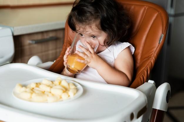 Śliczna młoda dziewczyna pije sok