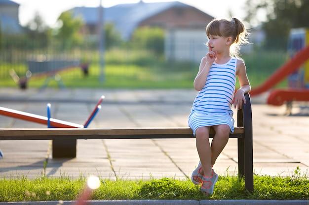 Śliczna młoda dziewczyna siedzi samotnie w krótkiej sukni