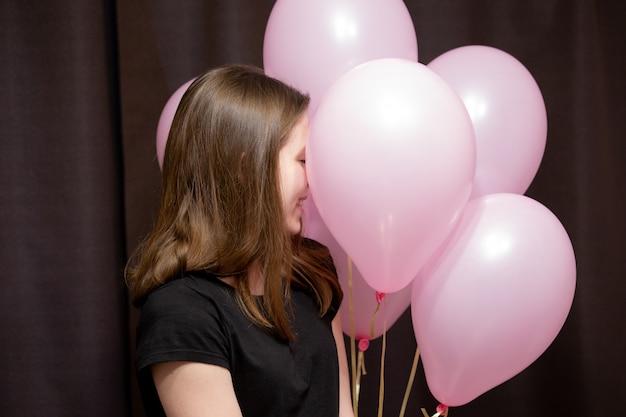 Śliczna młoda dziewczyna stoi przed swoimi różowymi kulkami, które trzyma i uśmiecha
