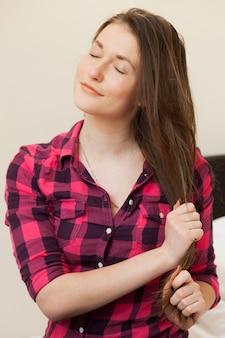 Śliczna młoda dziewczyna trzyma jej włosy