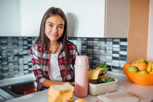 Śliczna młoda dziewczyna uśmiecha się i trzyma zdrową kanapkę nad swoim pudełkiem na drugie śniadanie