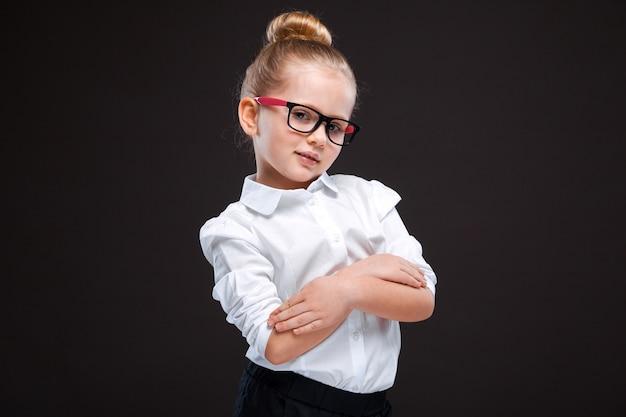 Śliczna młoda dziewczyna w białej koszula i czarnych spodniach