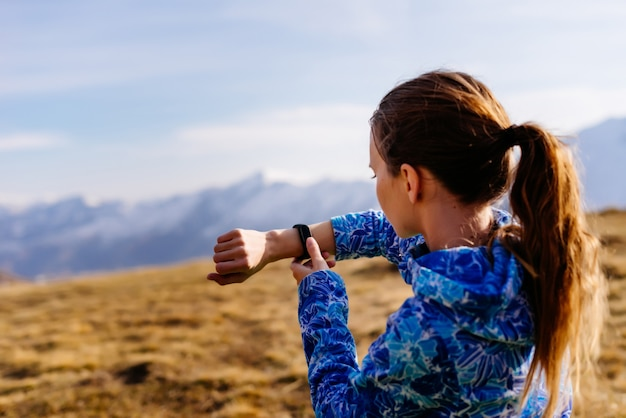 Śliczna młoda dziewczyna w niebieskiej kurtce podróżuje przez góry kaukazu, ogląda czas na zegarku