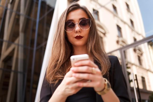 Śliczna młoda dziewczyna w okularach przeciwsłonecznych używa smartphone. stylowa dama używa do komunikacji smartfona