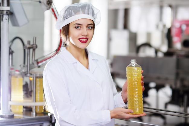Śliczna młoda dziewczyna z butelką słonecznika lub oliwy z oliwek