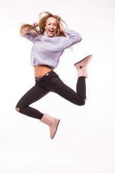 Śliczna młoda dziewczyna z dżinsami i różową górą skoki energicznie odizolowana