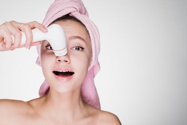 Śliczna młoda dziewczyna z różowym ręcznikiem na głowie robi głębokie oczyszczanie skóry twarzy za pomocą elektrycznej szczoteczki