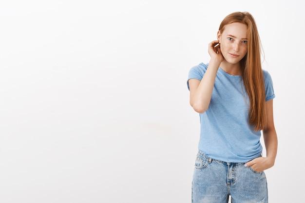 Śliczna młoda europejska rudowłosa kobieta z piegami, strzepująca włosy za uchem, trzymająca rękę w kieszeni i wpatrująca się z nieśmiałym i niezręcznym wyrazem twarzy