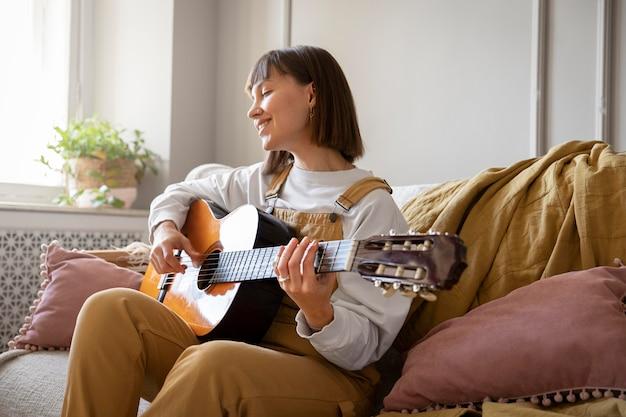 Śliczna młoda kobieta gra na gitarze w pomieszczeniu