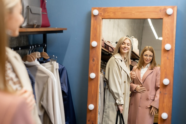 Śliczna młoda kobieta i jej matka stoją przed lustrem w butiku, podczas gdy kobieta w średnim wieku przymierza nowy elegancki płaszcz