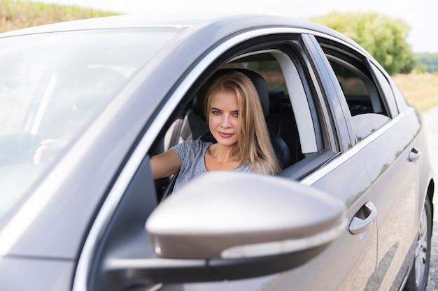 Śliczna młoda kobieta jedzie samochód