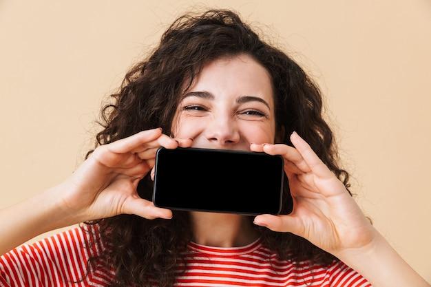 Śliczna młoda kobieta kręcone pokazuje wyświetlacz przez telefon komórkowy obejmujące usta.