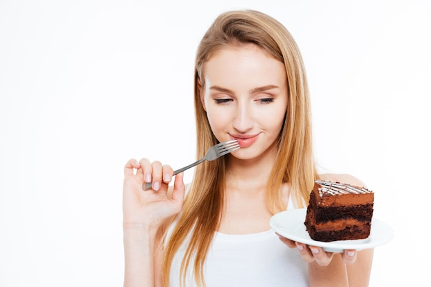 Śliczna młoda kobieta myśli i trzyma widelec i kawałek ciasta na białym tle