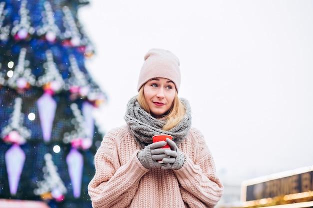 Śliczna młoda kobieta nosi kapelusz i różowy sweter i pije gorącą czekoladę