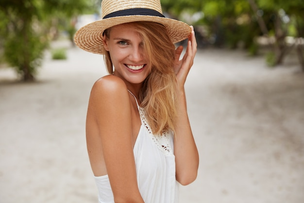 Śliczna młoda kobieta o promiennym uśmiechu, opalona, zdrowa skóra i atrakcyjny wygląd, lubi letni wypoczynek w rajskim miejscu, nosi słomkowy kapelusz, sympatycznie się uśmiecha. koncepcja ludzi, piękna i sezonowego odpoczynku
