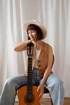 Śliczna młoda kobieta pozuje z gitarą w pomieszczeniu