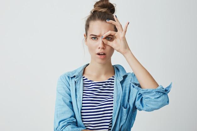 Śliczna młoda kobieta robi monoklowi gestowi i patrzeje przez palców