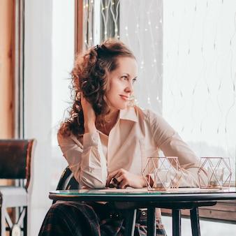 Śliczna młoda kobieta siedzi przy stole w kawiarni