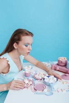 Śliczna młoda kobieta siedzi przy stole z plastikowymi naczyniami i piankami
