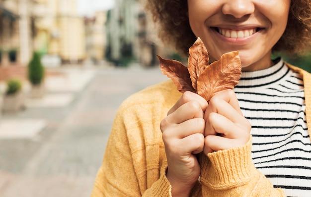 Śliczna młoda kobieta trzyma liść