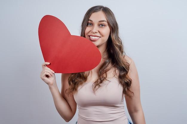 Śliczna młoda kobieta trzyma w ręku czerwone papierowe serce, uśmiechając się, patrząc w kamerę, na szarym tle. szczęśliwych walentynek. światowy dzień serca.