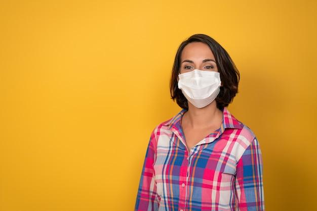 Śliczna młoda kobieta ubrana w białą maskę ochronną na białym tle na żółtym tle