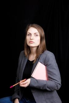 Śliczna młoda kobieta ubrana w biznesową kurtkę, trzymająca w ręku różowy notatnik