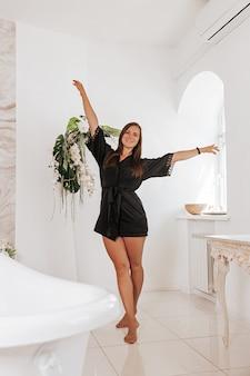 Śliczna młoda kobieta ubrana w czarny szlafrok spędza czas w łazience. szczęśliwa kobieta rano w łazience