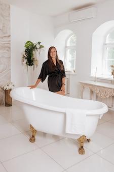 Śliczna młoda kobieta ubrana w czarny szlafrok spędza czas w łazience.