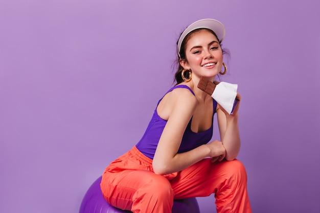 Śliczna młoda kobieta uśmiecha się i pozuje z tabliczką czekolady na fioletowej ścianie
