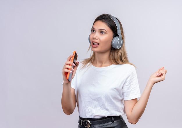 Śliczna młoda kobieta w białej koszulce, nosząca słuchawki, śpiewa podczas słuchania muzyki w telefonie na białej ścianie