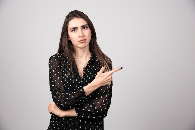 Śliczna młoda kobieta, wskazując palcem na szarej ścianie.