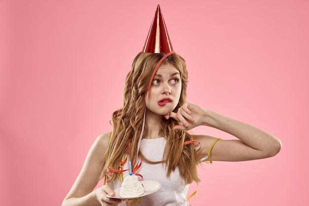 Śliczna młoda kobieta z babeczką i świecami obchodzi urodziny