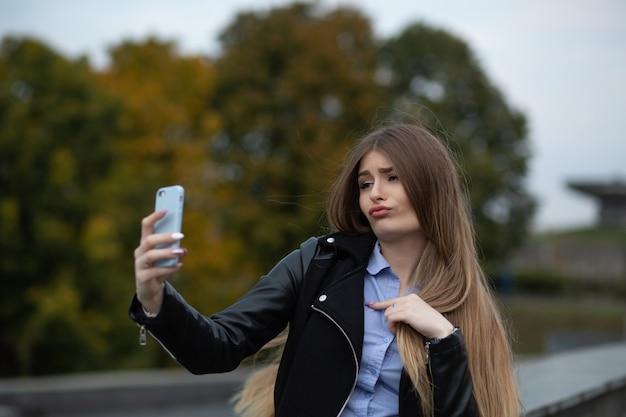 Śliczna młoda kobieta z długimi włosami, krzywiąc się i robiąc autoportret na telefonie komórkowym w parku