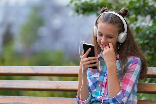 Śliczna młoda kobieta z słodkim uśmiechem siedzi na ławce na świeżym powietrzu, słuchając jej muzyki na słuchawkach