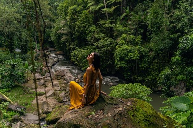 Śliczna młoda kobieta z uśmiechem na twarzy, patrząca w górę na egzotyczne rośliny w dżungli