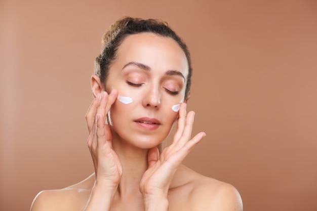 Śliczna, młoda kobieta z zamkniętymi oczami nakłada na twarz nowy krem liftingujący, jednocześnie dbając o skórę po jej umyciu