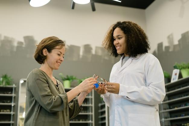 Śliczna, młoda konsultantka sklepu optycznego, pokazując jednemu z klientów nowe okulary i pomagając jej w wyborze