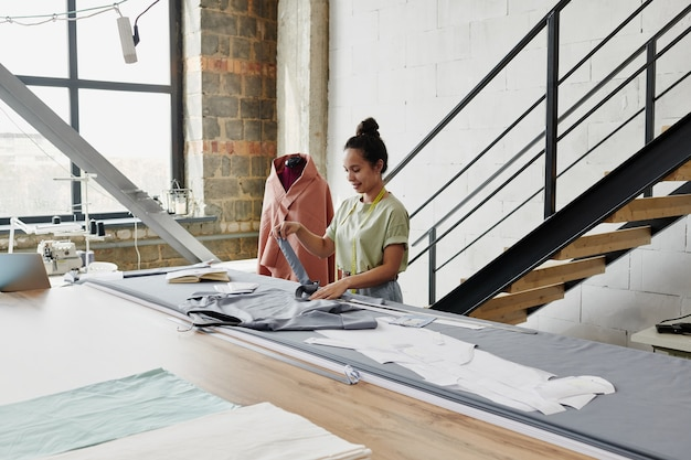 Śliczna młoda krawcowa pracująca nad nowym zamówieniem klienta lub własną kolekcją ubrań, robiąc w studio pasek do szarej sukienki przy stole