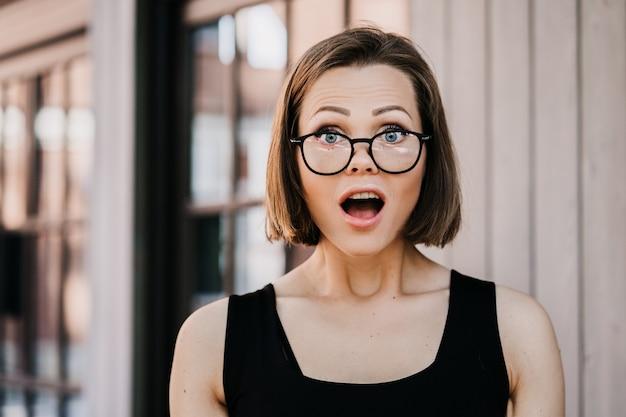 Śliczna młoda krótkowłosa kobieta w szkłach ubierał przypadkowego, szokującego wiadomość z szeroko otwartymi oczami i usta plenerowymi.
