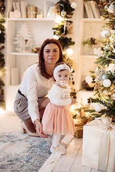 Śliczna młoda mama i jej córeczka siedzą obok choinki w swoim domu. koncepcja świąt bożego narodzenia