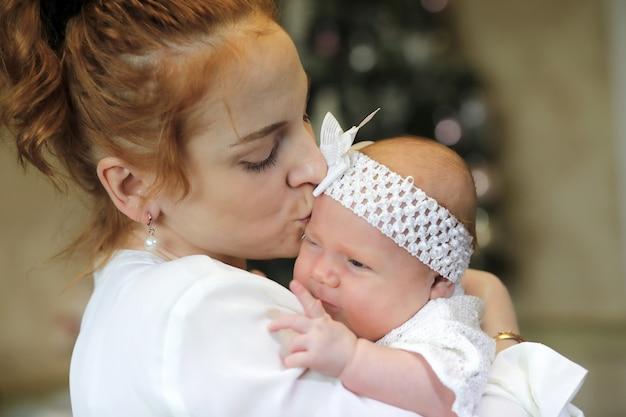 Śliczna młoda matka trzymająca w ramionach nowonarodzoną córkę
