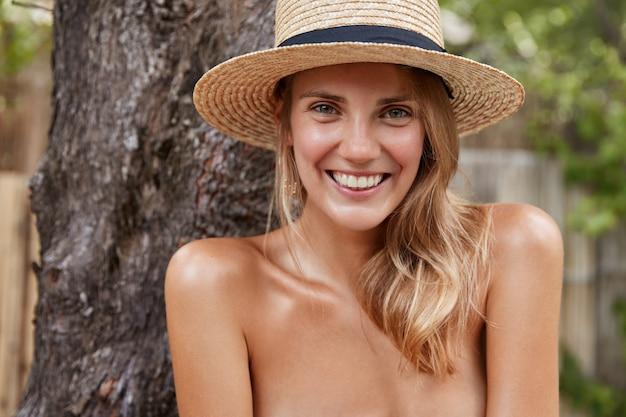 Śliczna, młoda modelka o nagim ciele i zdrowej, czystej skórze spędza wolny czas w tropikalnej lagunie, nosi letni kapelusz, zadowolona z dobrego wypoczynku. pojęcie piękna i szczęścia