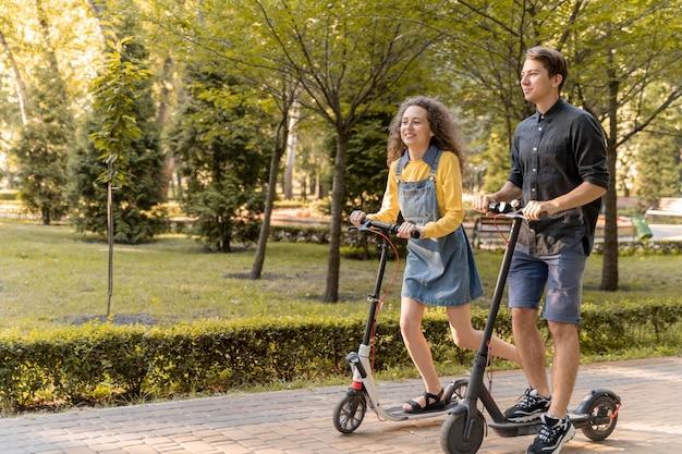 Śliczna młoda para jedzie skuterem na zewnątrz