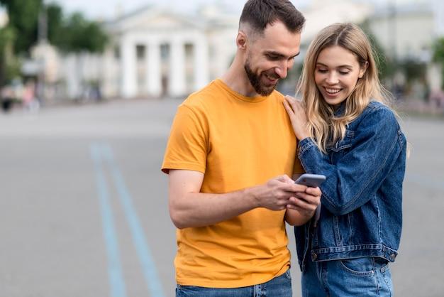 Śliczna młoda para patrząc na telefon
