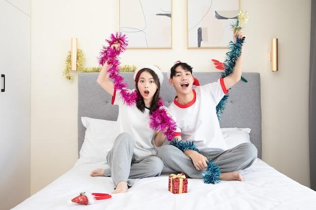 Śliczna młoda para świętuje boże narodzenie na łóżku
