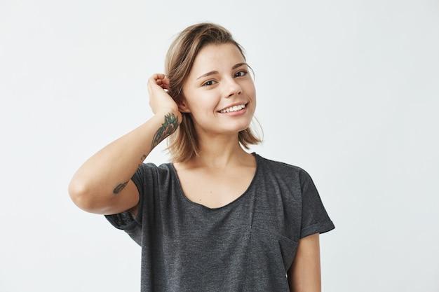 Śliczna młoda piękna dziewczyna uśmiecha się korygujący włosy.