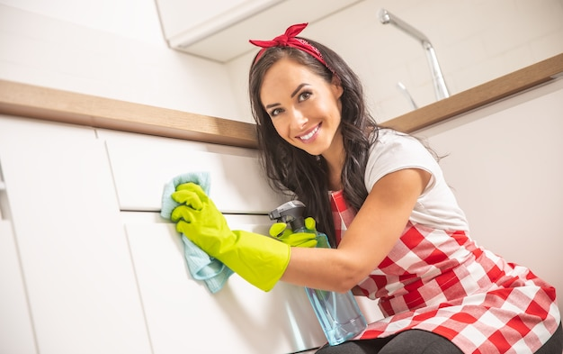 Śliczna młoda pokojówka w fartuchu czyszczenie białych drzwi szafki kuchennej szmatką i detergentem w żółtych gumowych rękawiczkach.