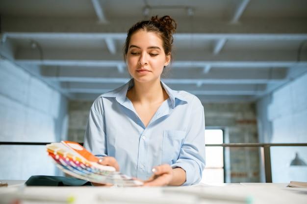 Śliczna, młoda projektantka kreacji przyglądająca się palecie kolorów w dłoni, wybierając próbki do nowej kolekcji mody