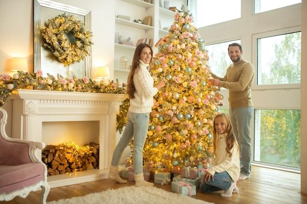 Śliczna młoda rodzina dekorowanie choinki w domu